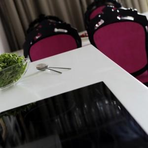 Z białym blatem kuchennym efektownie kontrastuje czarna płyta grzewcza. Proste linie i gładkie powierzchnie są nowoczesnym akcentem we wnętrzu, podczas gdy stylizowane krzesła to ukłon w stronę stylistyki glamour. Projekt: Chalupko Design. Fot. Chalupko Design.