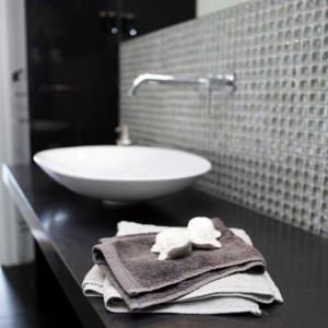 Delikatne, opływowe linie umywalki nablatowej kontrastują z ostrymi, prostymi krawędziami szafki i prostego, bezramowego lustra. Kompozycja różnorodnych kolorów i materiałów nadaje łazience luksusowy charakter. Projekt: Chalupko Design. Fot. Chalupko Design.