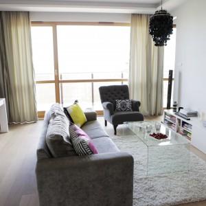 Przytulna, miękka sofa, stylizowany tapicerowany fotel i miękki dywan budują w salonie przytulny klimat. Na ściance działowej oddzielającej salon od sypialni zawieszono telewizor. Szafka RTV komponuje się kolorystycznie ze ścianą. Z czernią ekranu harmonizuje czarny, dekoracyjny żyrandol. Projekt: Chalupko Design. Fot. Chalupko Design.