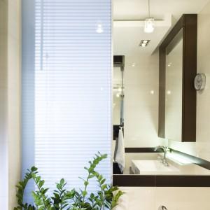 Lustra dobrze powiększają małą łazienkę, ale skuteczne są dzięki dużej ilości lustrzanych płaszczyzn: nad lustrem, nad wanną i jako lustrzane fronty szafy na przeciwko. Projekt: Magdalena Kuklińska. Fot. Tomasz Markowski.