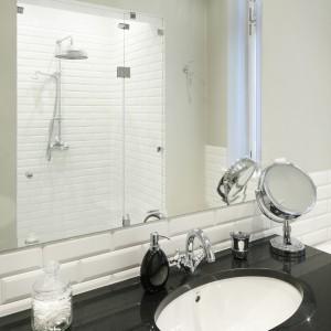 W lustrze odbija się wnęka prysznicowa. prysznic we wnęce to dobre rozwiązanie do małych łazienek. W przeciwieństwie do kabin nie zajmują wizualnej przestrzenie pomieszczenia. Projekt: Iwona Kurkowska. Fot. Bartosz Jarosz.
