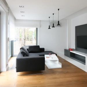 Trzy czarne, minimalistyczne lampy sufitowe umieszczono między sofą, a ścianą telewizyjną. Dzięki temu uzyskano optymalne oświetlenie ekranu. Projekt: Katarzyna Kiełek, Agnieszka Komorowska-Różycka. Fot. Bartosz Jarosz.