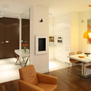 Strefa wejścia w eleganckim apartamencie urządzono została w bieli, którą ociepla drewno w ciepłym wybarwieniu. Projekt: Małgorzata Galewska. Fot. Bartosz Jarosz.