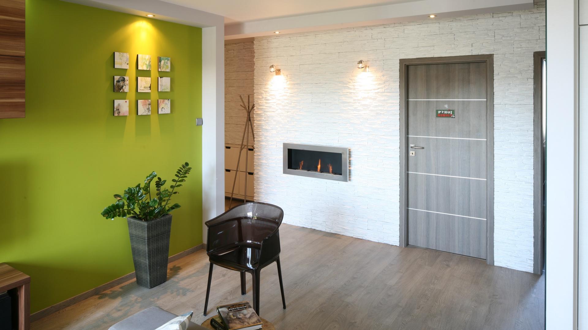 W niewielkim mieszkaniu strefa wejścia przybrała salonowy charakter. Świadczy o tym udekorowana kamieniem ściana oraz elegancki biokominek. Projekt: Arkadiusz Grzędzicki. Fot. Bartosz Jarosz.