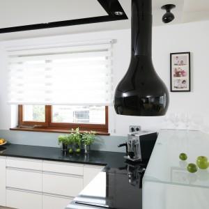 Przestrzeń kuchni zdominowała biel. Obecna jest ona zarówno na frontach mebli, jak ina powierzchni ścian. Jej jednostajny wymiar przełamuje czarny  blat wykonany zgranitu oraz pas wyznaczający podwieszenie sufitu. Projekt: Michał Mikołajczak. Fot. Bartosz Jarosz.