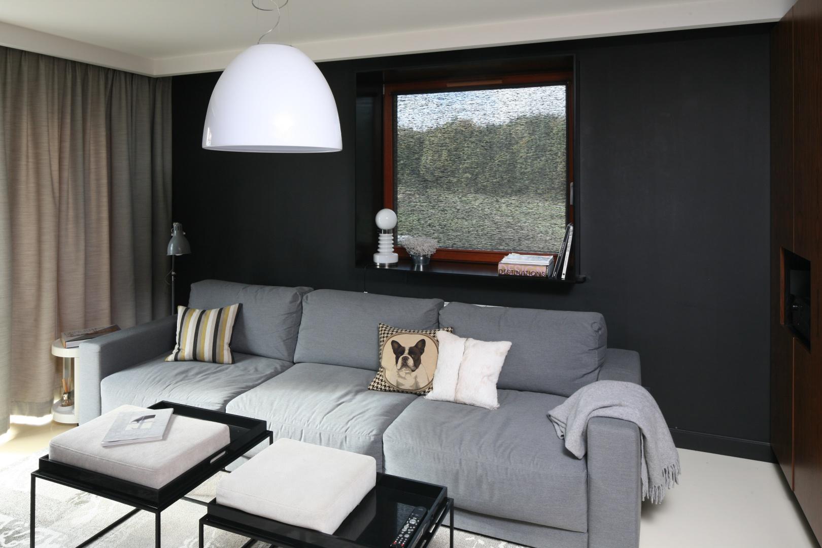 Chociaż szara, to jednak jest najjaśniejszym detalem w salonie. Na tle czarnej ściany nowoczesna kanapa prezentuje się bardzo efektownie. Projekt: Katarzyna i Michał Dudko. Fot. Bartosz Jarosz.