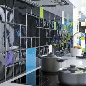 Ścianę nad blatem pokryto płytkami ceramicznymi o różnych rozmiarach, strukturze i kolorach. Dominującą czerń ożywiają żywe kolory zieleni i błękitu. Fot. Ceramika Paradyz, kolekcja Reflette.