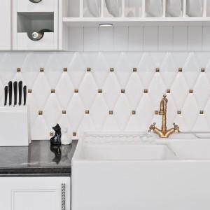 Elegancka kuchnia w przepychu wymaga odpowiednich materiałów nad blatem kuchenny. Seria płytek Carat to ceramiczne płytki o fantazyjnym kształcie wielokątów, połączone z małymi złotymi elementami dekoracyjnymi. Fot. Dunin.