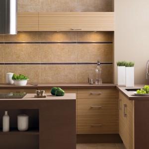 Płytki ceramiczne z kolekcji Opirus to piękne ciepłe, piaskowe kolory. Ułożone nad blatem kuchennym estetycznie komponują się z przytulną barwą mebli kuchennych. Poszczególne rzędy płytek odgranicza estetyczna listwa w ciemniejszym kolorze i stalowej obwódce. Fot. Opoczno.