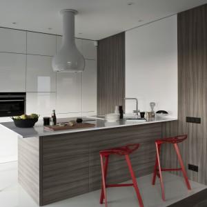 Kuchnia utrzymana w kolorach bieli i kawy z mlekiem została ożywiona przez obecność czerwonych, nowoczesnych hokerów. Proste linie mebli kuchennych komponują się efektownie z fantazyjnym designem krzeseł. Fot. ZAJC kuchnie.
