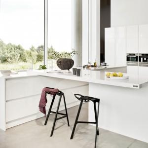 Nowoczesna biała kuchnia zyskała mocniejszy akcent, dodający jej charakteru, w postaci czarnych krzeseł, ustawionych przy efektownym półwyspie. Duży, biały blat został posadowiony na białej płycie. Ciekawa geometryczna forma pozostawia dużo miejsca pod blatem barowym. Fot. ZAJC kuchnie.