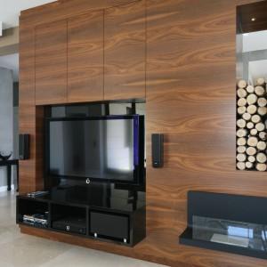 W przestronnym salonie postawiono na oryginalny wystrój o ekskluzywnym charakterze. Szafka RTV została w pełni zintegrowana z całą zabudową ścianki z telewizorem wykonane z forniru w ciepłym wybarwieniu drewna. Projekt: Katarzyna Koszałka. Fot. Bartosz Jarosz.