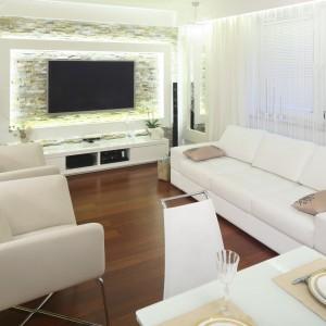 Niewielki salon urządzono w bieli, co pozwoliło optycznie powiększyć jego przestrzeń. W tym kolorze dobrano również niską szafkę RTV, nad która wyeksponowano telewizor. Projekt: Małgorzata Mazur. Fot. Bartosz Jarosz.