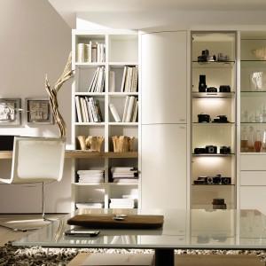 Elegancka meblościanka wykonana z dębu lakierowanego na biało. Połączenie witryny i półek z oryginalnym, niedużym biurkiem umożliwia subtelne połączenie dwóch funkcji: biura i salonu w jednym wnętrzu. Fot. Hülsta.