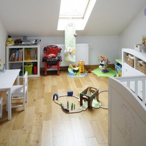 Na poddaszu urządzono pokój dziecięcy. Dominują w nim jasne barwy, stanowiące idealną bazę dla kolorowych zabawek, które wypełniły przestrzeń. Projekt: Magdalena Wielgus-Biały, Jacek Biały. Fot. Bartosz Jarosz.