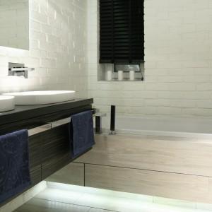 Ściana nad wanną, podobnie jak pozostałe ściany  w tej łazience została wykończona cegłą. Jej powierzchnię pokryto polecaną do zastosowania w łazience farbą ceramiczną. Projekt: Dominik Respondek. Fot. Bartosz Jarosz.