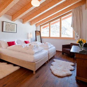 Naturalne materiały to nieodłączny element wystroju zimowych kurortów.Drewniana podłoga oraz sufit ocieplają wnętrze sypialni. Fot. Chalet Zeus/Alpine Guru.