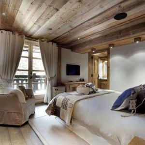 Przestronna sypialnia zachęca do odpoczynku. Jasne ściany w połączeniu z surowym drewnem tworzą przytulne wnętrze. Fot. The Petit Chateau Courchevel.