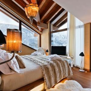 Piękne widoki za oknem współgrają z wystrojem sypialni. Naturalne drewno, starannie dobrane dodatki tworzą przytulne wnętrze. Fot. Chalet Zermatt Peak.