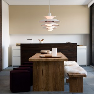 Kuchnię od jadalni symbolicznie oddziela wyspa, kontrastująca kolorystycznie z jasnym umeblowaniem kuchni. Drewniany dekor komponuje się z drewnianymi meblami w jadalni, a oba pomieszczenia spaja jednorodna posadzka na podłodze. Fioletowe pufy, pełniące rolę mebli jadalnianych, stanowią preludium do kanapy, ustawionej w kąciku wypoczynkowym. Projekt: arch. Laura Consiglio, arch. Francesca Menga/Carlo Donati Studio. Fot. Carlo Donati Studio.