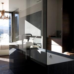 Strefę sypialni i łazienki zlokalizowano w bezpośrednim sąsiedztwie. Obie funkcje tworzą wspólną przestrzeń wypoczynku i relaksu. Jasne meble w sypialni kontrastują z wanną w ciemnej, kamiennej obudowie i hebanowym drewnem wokół strefy umywalki. Wolno stojąca wanna w centrum pomieszczenia, odgrodzona jest dyskretnym szklanym panelem. Projekt: arch. Laura Consiglio, arch. Francesca Menga/Carlo Donati Studio. Fot. Carlo Donati Studio.