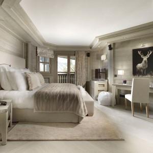 Przestronna sypialnia w stonowanych, spokojnych odcieniach. Jasne drewno z wyraźnym rysunkiem, drewniane meble oraz grube tkaniny to obowiązkowe elementy wnętrz górskich wnętrz urządzonych w stylu chalet. Fot. Chalet Karakoram Courchevel.