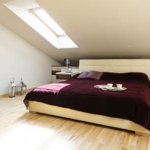 Białe, tapicerowane łóżko doskonale komponuje się z jasnymi meblami oraz podłogą o ciepłej barwie. Spójne, dekoracyjne lampki nocne, kinkiety dodają wnętrzu uroku i wprowadzają elementy eleganckiego stylu glamour. Fot. Bartosz Jarosz.