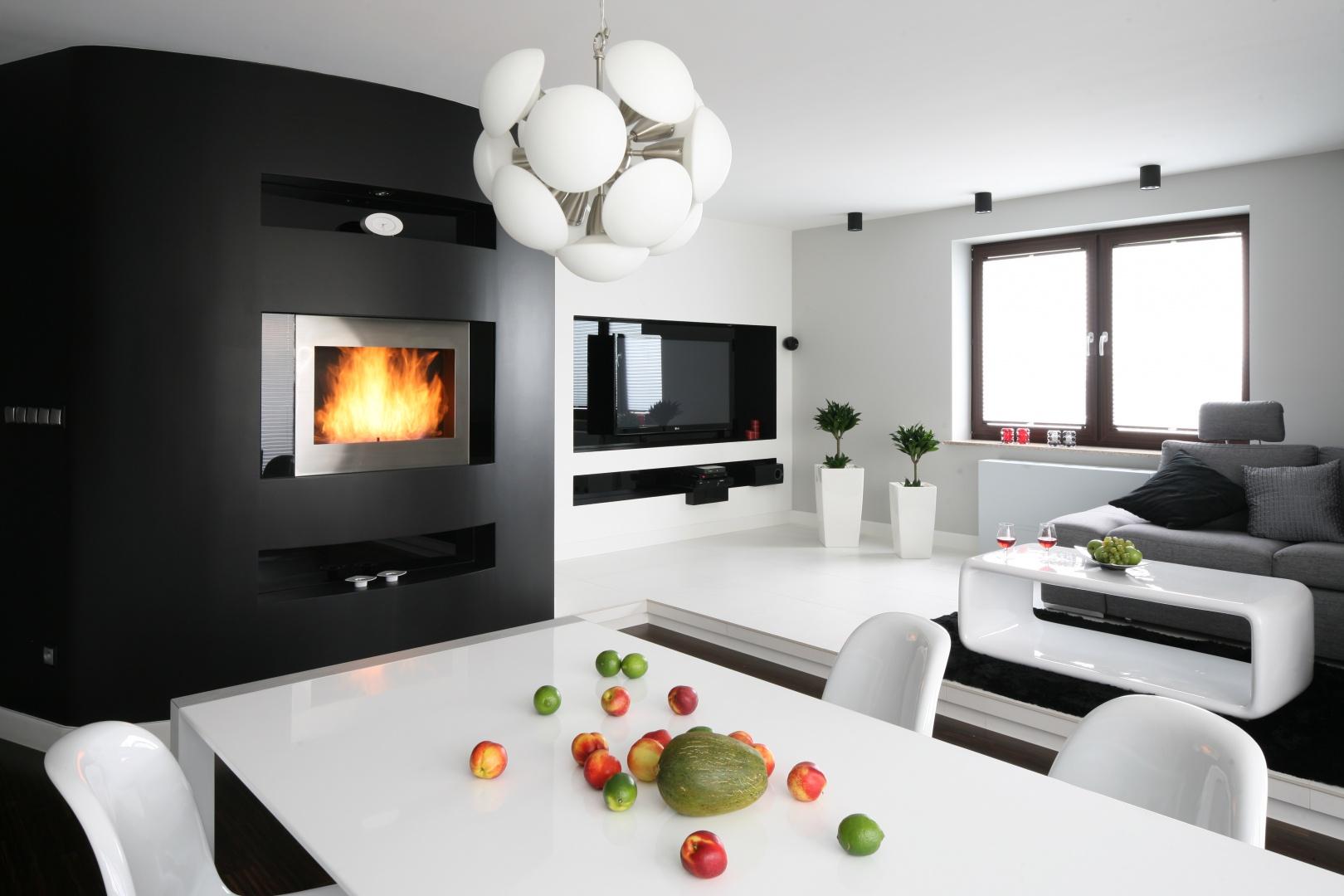 Białe ściany są idealnym tłem dla ciemnych elementów wyposażenia. Dla podkreślenia piękna ognia, ścianę z kominkiem pomalowano na czarno, czym przełamano jasną aranżację. Projekt: Agnieszka Burzykowska-Walkosz. Fot. Bartosz Jarosz.