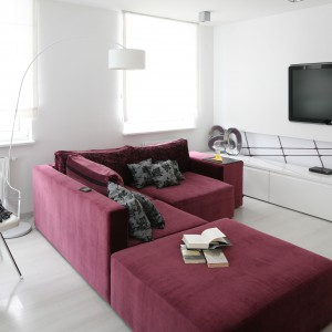 Białe ściany sprawiają, że pokój wydaje się bardziej przestronny. Są także znakomitym tłem dla burgundowej kanapy, będącej centralnym elementem wyposażenia. Projekt: Anna Sokołowska. Fot. Bartosz Jarosz.