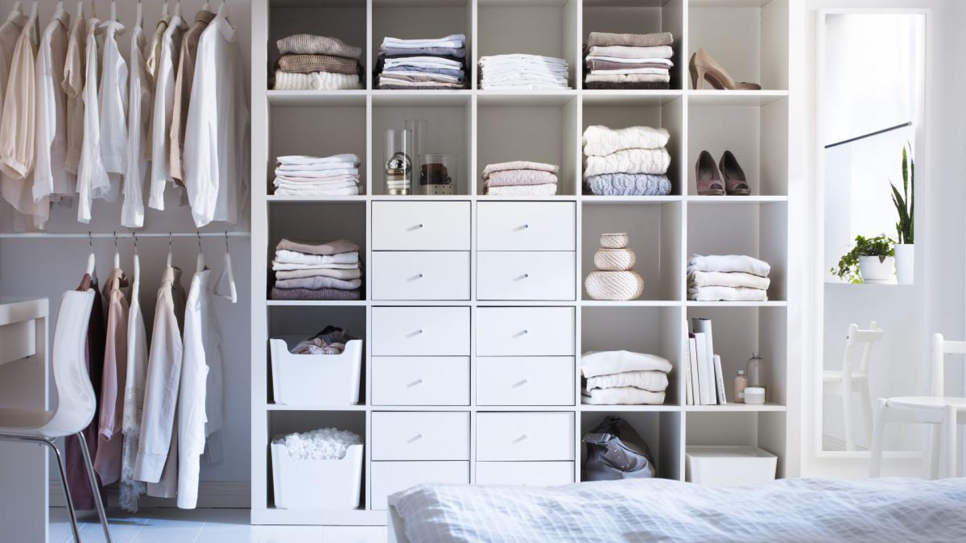 Garderobę na mniejszej przestrzeni możemy złożyć z poszczególnych elementów. Na zdjęciu: regał Expedit z wkładami zawierającymi szuflady oraz przymocowane do ściany drążki na ubrania. Fot. IKEA
