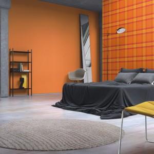 Żywa, pomarańczowa kolorystyka tapety dobrze komponuje się z szarością łóżka oraz jasną podłogą.Fot. Rasch.