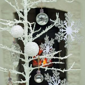 Przezroczyste szklane bombki i zawieszki w formie błyszczącej śnieżnej kuli będą się świetnie prezentowały w towarzystwie uroczych zawieszek w kształcie płatków śniegu oraz bombek imitujących szyszki. Fot. Parlane.