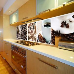 Ściana nad blatem może kontrastować z meblami kuchennymi lub też podkreślać ich kolorystykę. W tej ciepłej, przytulnej kuchni, gdzie dominują brązy i beże, kawowe motywy na ścianie są subtelnym uzupełnieniem całej aranżacji wnętrza. Fot. DecoMania.