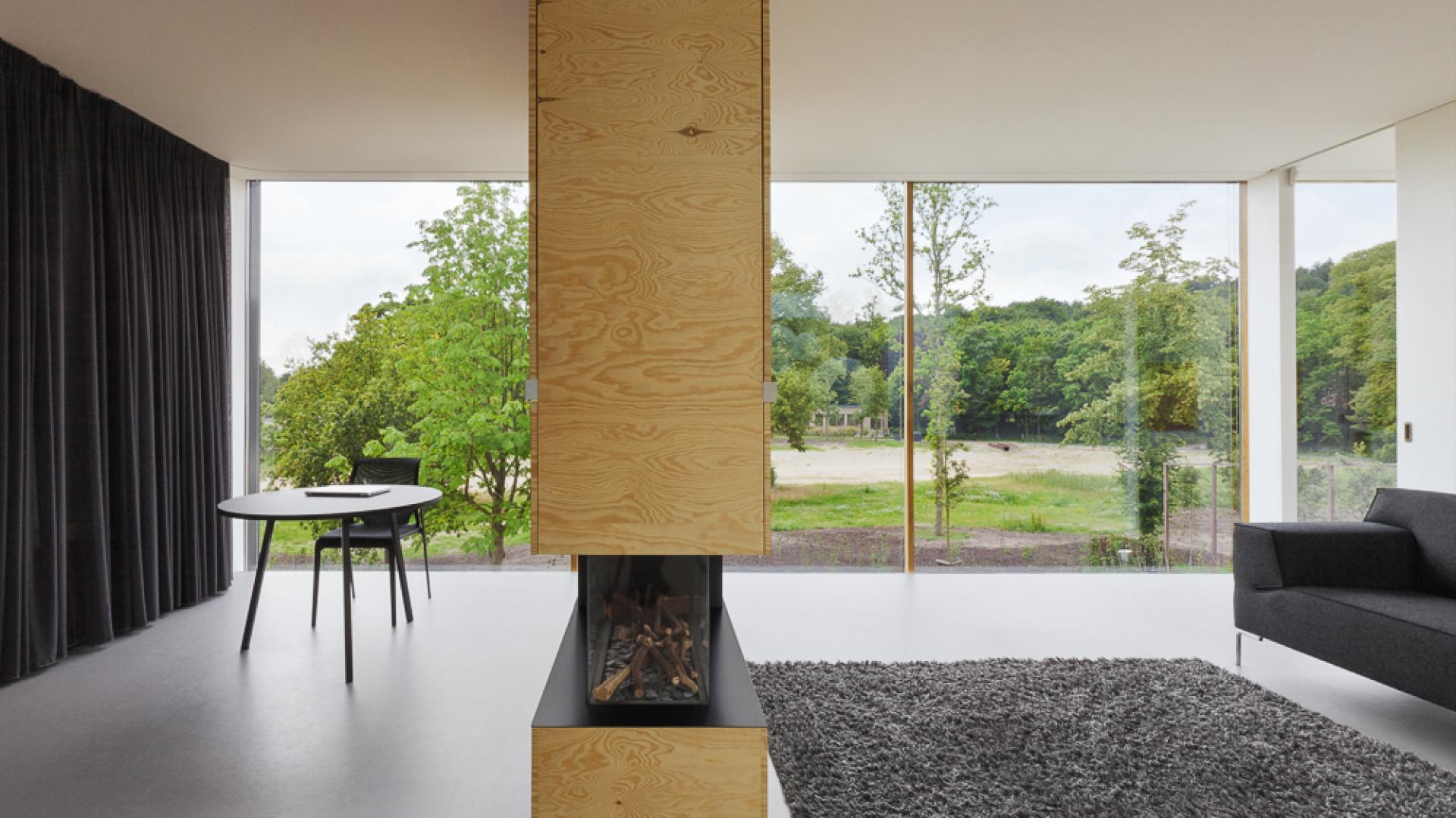 Przeszklone ściany rozświetlają wnętrze, zapewniają piękny widok na otaczającą naturę a także dodają lekkości przestrzeni domu. Kominek na przestał pełni funkcję elementu działowego oraz równomiernie rozprowadza ciepło w pomieszczeniach. Projekt: i29 interior architects. Fot. i29 interior architects.