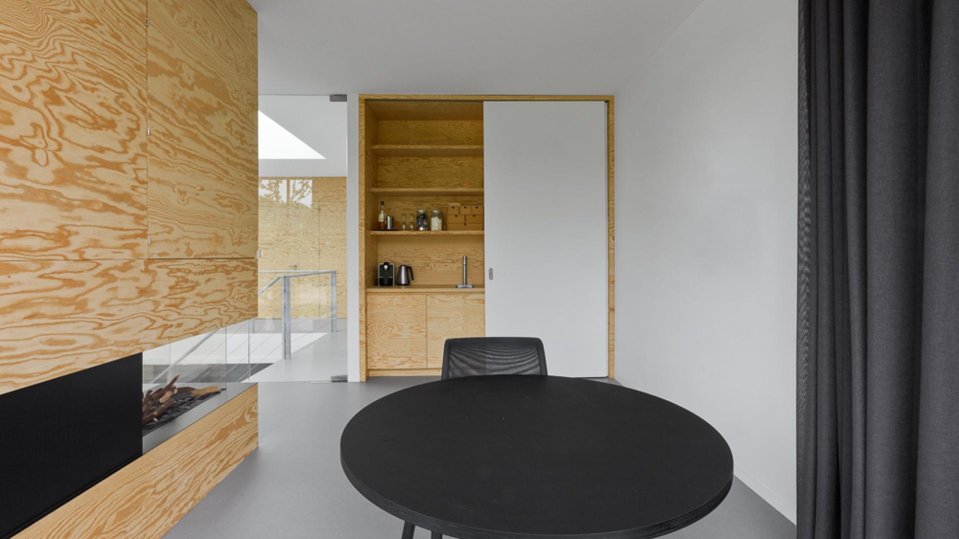 Funkcję ścianki działowej pomiędzy przestrzenią jadalni a salonu pełni kominek w efektownej obudowie z paneli z sosnowego drewna. W ścianie