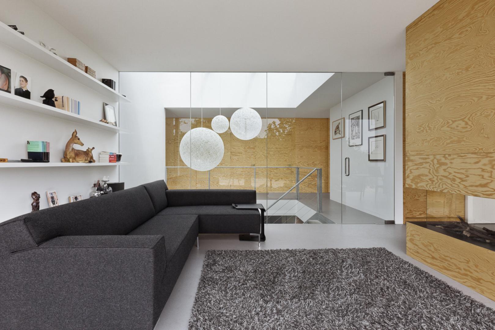 Przytulny klimat w salonie buduje miękki dywan, wygodny narożnik oraz - oczywiście - komimnek. Wnętrze rozświetla i optycznie powiększa biel na ścianach oraz przeszklone drzwi, prowadzące do klatki schodowej. Projekt: i29 interior architects. Fot. i29 interior architects.