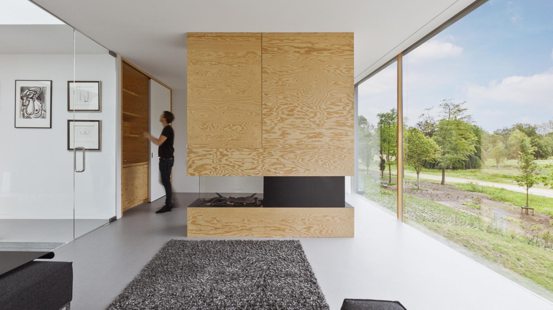 We wnętrzach panuje estetyczny minimalizm. Proste linie i gładkie powierzchnie harmonizują z niewielką ilością dekoracji i szklanymi drzwiami, nadającymi lekki charakter wnętrzu. Przytulniejszym akcentem jest miękki dywan w salonie. Projekt: i29 interior architects. Fot. i29 interior architects.