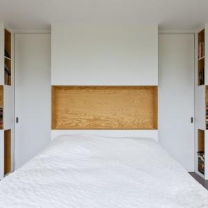 Ścianę za łóżkiem w sypialni zabudowano praktyczną zabudową z licznymi półkami i schowkami. Część powierzchni pomalowano - na wzór ścian - czystą bielą, podczas gdy resztę pozostawiono w naturalnym kolorze sosnowego drewna. Jasnobrązowa barwa ociepla wnętrze, w którym dominuje biel. Projekt: i29 interior architects. Fot. i29 interior architects.