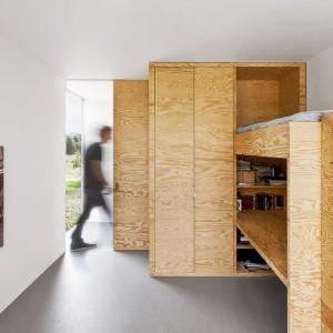 Architekci znaleźli masę zastosowań dla materiału jakim jest drewno. Tutaj szafki przechodzą w piętrowe łóżko. Wszystko wykonane z sosnowych paneli. Projekt: i29 interior architects. Fot. i29 interior architects.