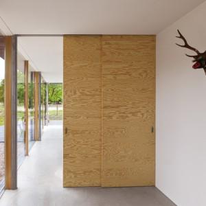 Dom powstał w duchu przyjaźni z naturą. Dialog z naturą nawiązują zarówno panoramiczne okna z widokiem na otoczenie domu, jak i designerski drewniany jelonek na ścianie, zamiast prawdziwego poroża upolowanej zwierzyny. Projekt: i29 interior architects. Fot. i29 interior architects.