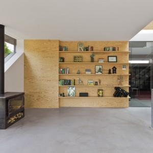 Część wnętrz domu zlokalizowano w piwnicy. Ze względu na niecodzienne położenie budynku, uzyskano oryginalny kształt bryły. Zaowocowało to również fantazyjnym kształtem okien. Na sąsiadującej z nimi ścianie, zlokalizowano praktyczny regał z licznymi półkami na dekoracje i pamiątki. Projekt: i29 interior architects. Fot. i29 interior architects.