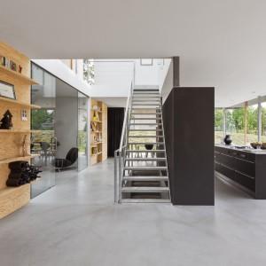 W piwnicy urządzono przestronną, nowoczesną kuchnię. Ścianka z zabudową kuchenną stanowi także bazę do lokalizacji schodów, prowadzących na piętro. Wyspa kuchenna z dużym, praktycznym blatem pozwala na przygotowywanie posiłków i podziwianie krajobrazu za oknem. Projekt: i29 interior architects. Fot. i29 interior architects.