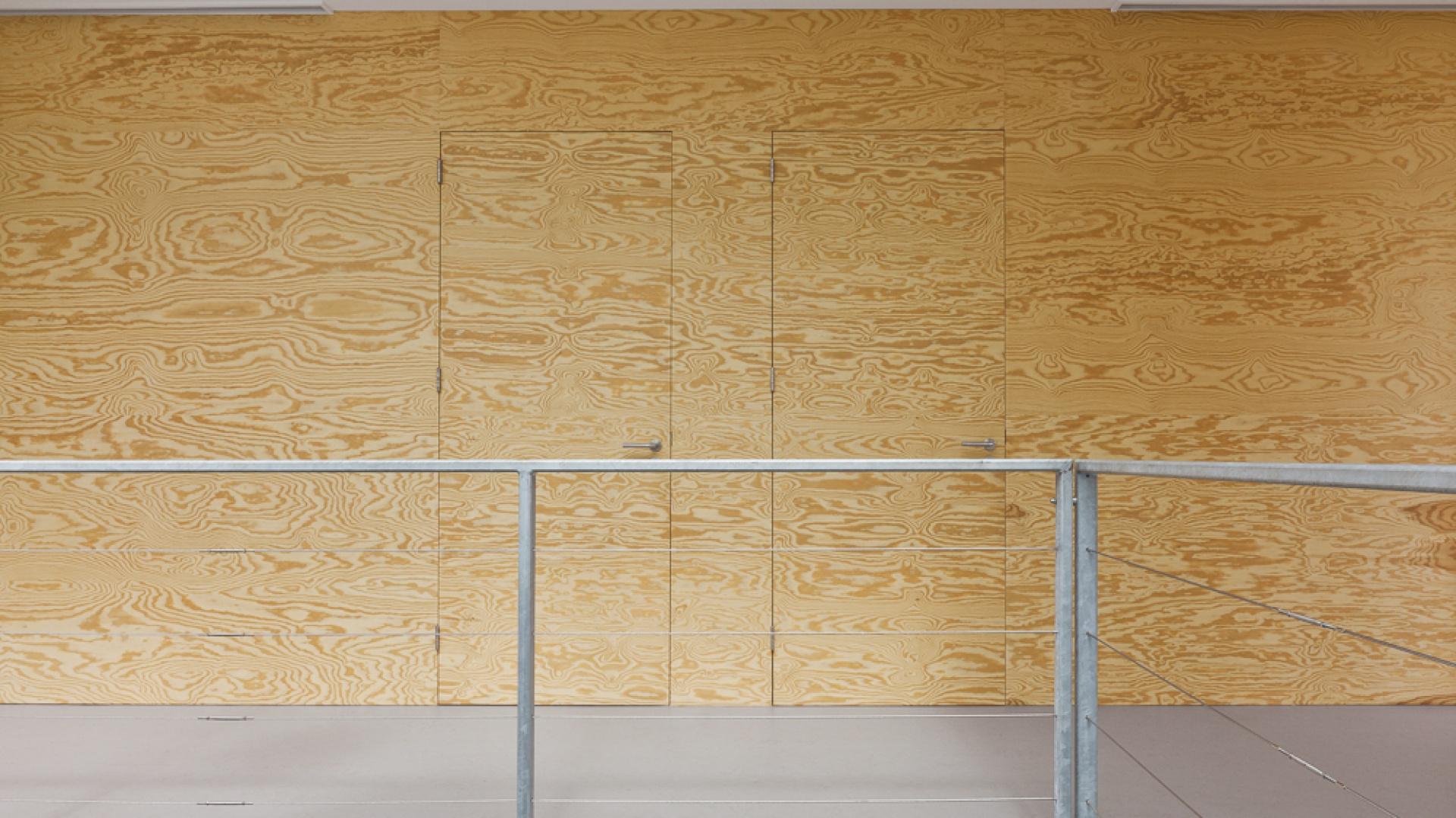 Zagadka dla spostrzegawczych: gdzie schowały się drzwi? Jednolitą powierzchnię przedpokoju na piętrze stworzono dzięki wykonaniu ścian i drzwi wejściowych do poszczególnych pomieszczeń z takich samych paneli drewnianych. Projekt: i29 interior architects. Fot. i29 interior architects.