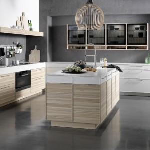 Jesionowy fornir pokrywa fronty tych pięknych mebli kuchennych, zwieńczonych białymi lakierowanymi frontami. Kompozycja jasnego, subtelnie chłodnego drewna z sterylną bielą idealnie pasują do oszczędnej, nowoczesnej stylistyki mebli. Fot. Rational, model Cadre.