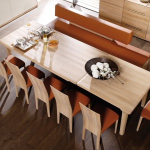 Pomarańczowa tapicerka krzeseł i nowoczesnej ławy sprawia, że jadalnia staje się jeszcze cieplejsza i zyskuje apetyczny wygląd. Fot. Voglauer.