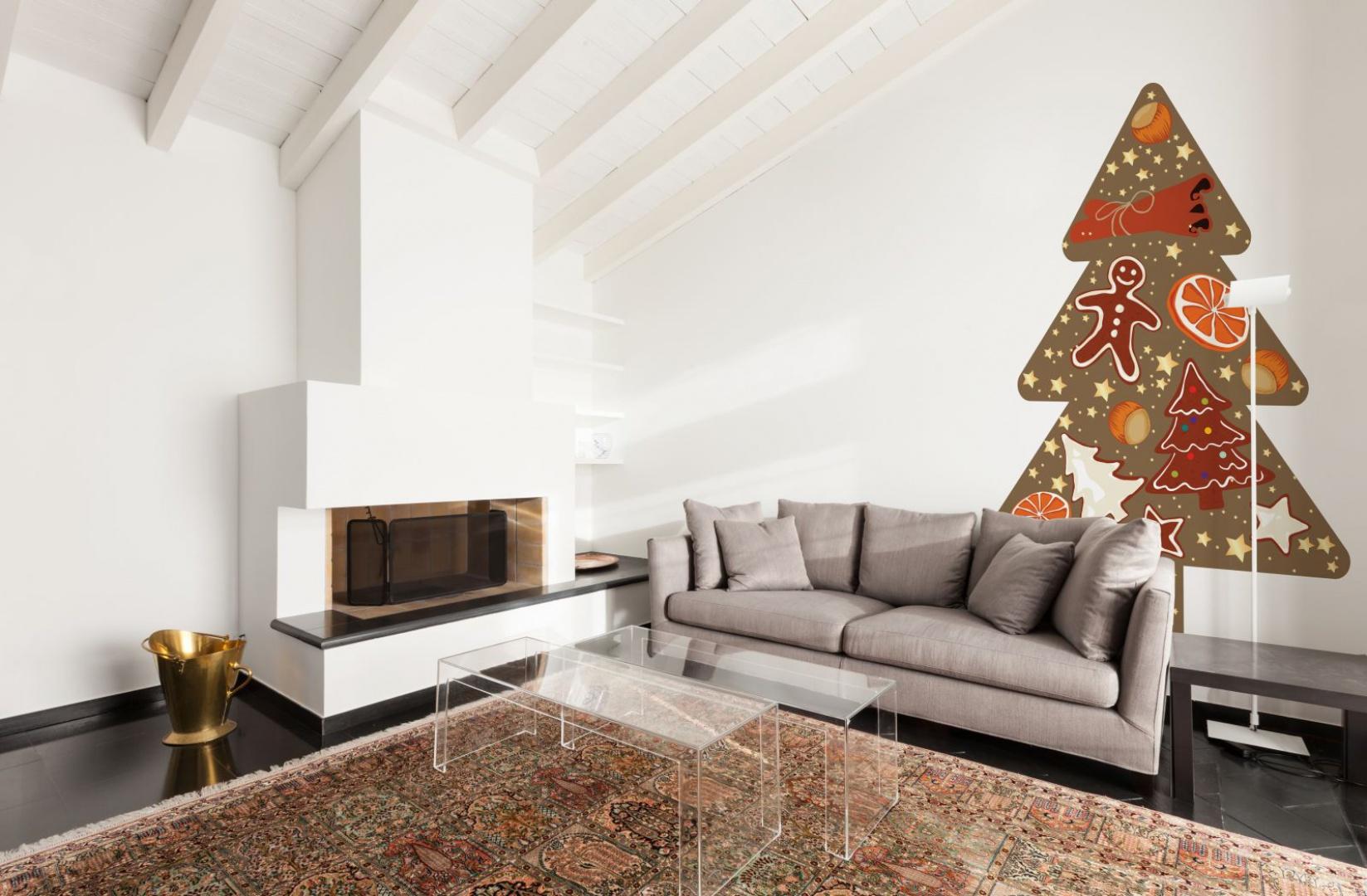 Dekoracja ścienna inspirowana choinką jest nie mniejszą dekoracją salonu niż świąteczne drzewko. zdobiące ją pierniki i plasterki pomarańczy komponują się z korzennym zapachem, jaki roztacza się w domu w te wyjątkowe dni. Fot. Minka.