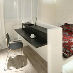W nogach łóżka zorganizowano dodatkowy mebel. Praktyczny wyciągany blat może tworzyć biurko do pracy lub toaletkę. Projekt: Dominik Respondek. Fot. Bartosz Jarosz.