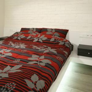 W sypialni - konsekwentnie z całym wnętrzem - dominują proste formy i stonowane barwy. Żywszym akcentem kolorystycznym są tekstylia na łóżku. Efektownym zabiegiem jest pas oświetlenia poprowadzony przy podłodze pod łóżkiem. Projekt: Dominik Respondek. Fot. Bartosz Jarosz.