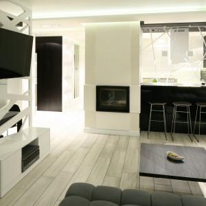 Na granicy salonu i kuchni jest słup konstrukcyjny z kominkiem, który stał się elementem pozwalającym na estetyczne i oryginalne wydzielenie kuchni. Projekt: Dominik Respondek. Fot. Bartosz Jarosz.