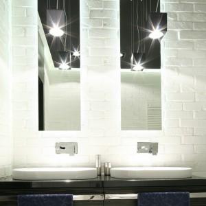 Surowe, nowoczesne wnętrze łazienki zostało ocieplone wykonaną na zamówienie szafką. Jej dekor stanowi egzotyczny fornir w ciemnym, głębokim odcieniu czekolady. Projekt: Dominik Respondek. Fot. Bartosz Jarosz.